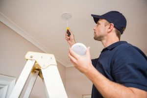 Man Checking Smoke Alarm on Ceiling