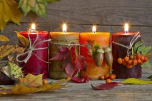 Burning Candles on Wooden Table Decorated for Fall